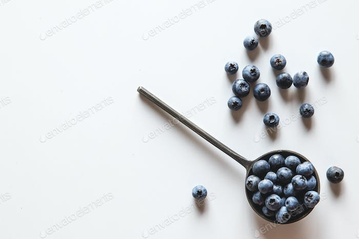 Blueberries in a spoons isolated on a white background. Healthy food, health