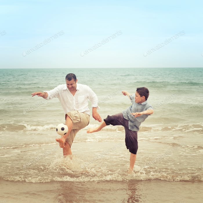 Father on the beach kicking the ball while his son tries to get