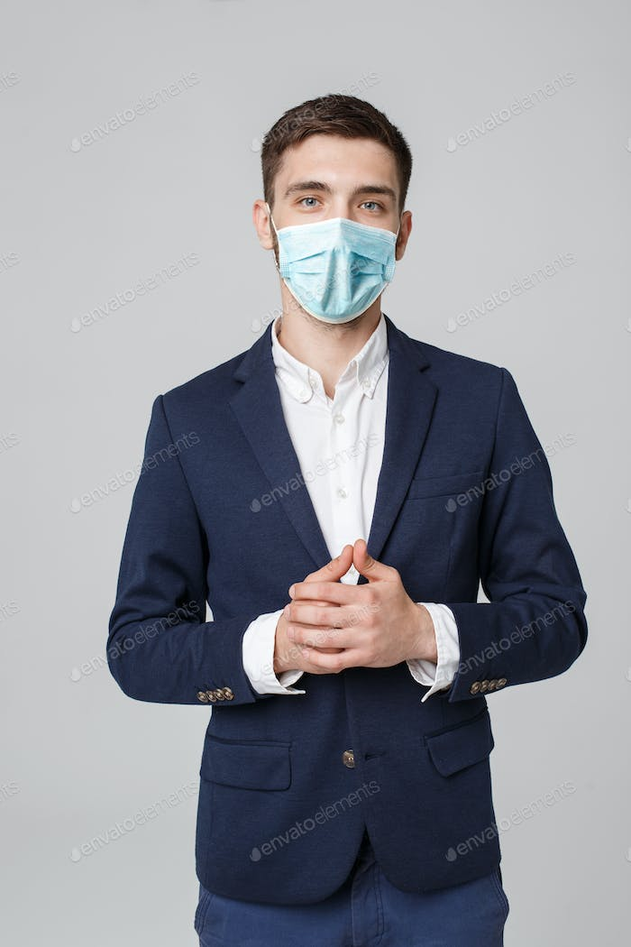 Business Concept - portrait young successful businessman in face mask osing over dark background