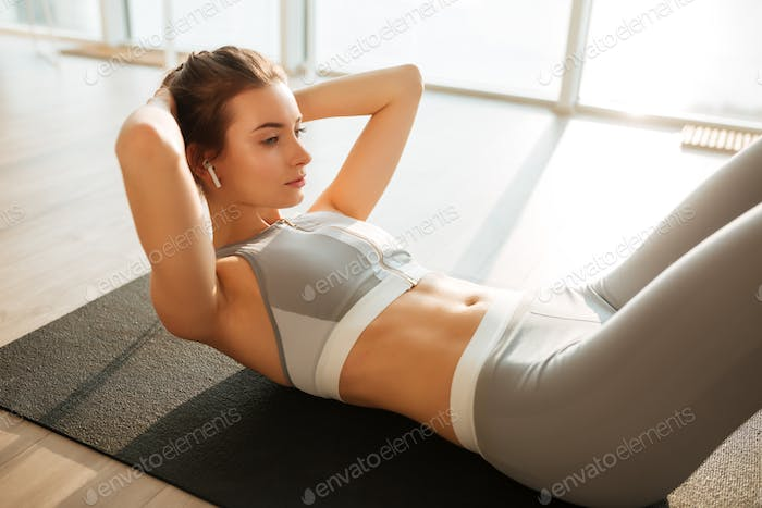 Thoughtful girl in sporty top and leggings lying on yoga mat rocking press listening music