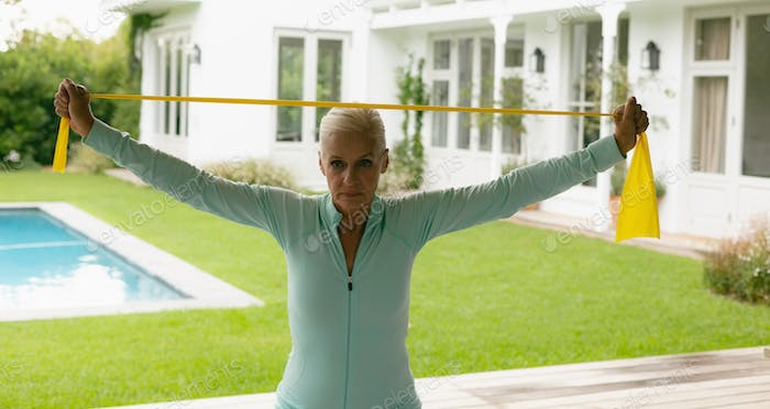 Front view of active senior Caucasian woman exercising with resistance band in porch at home