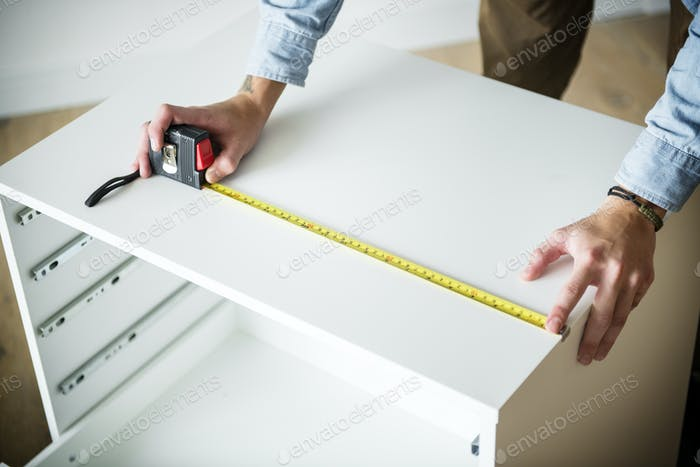 Man measuring the cabinet