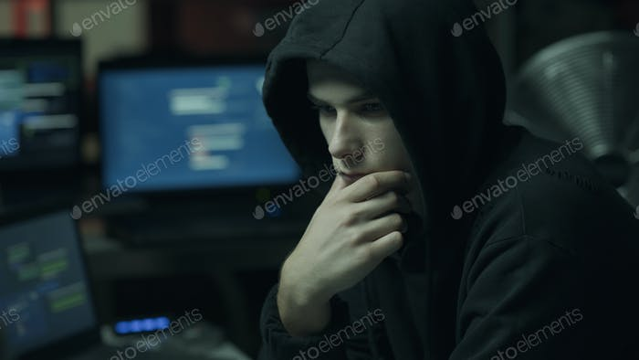 Hacker with hoodie working with a computer