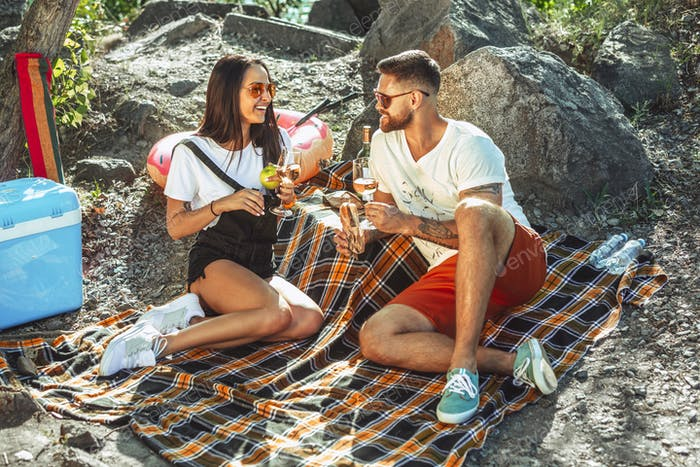 Young couple having picnic at riverside in sunny day