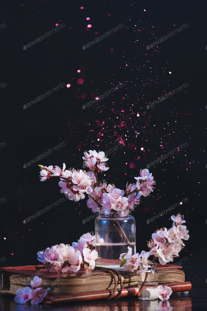 Spring cherry blossom in a glass jar on a dark background with pink sparkle. Creative flower