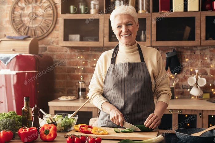 Cheerful senior woman cutting vegetables for salad