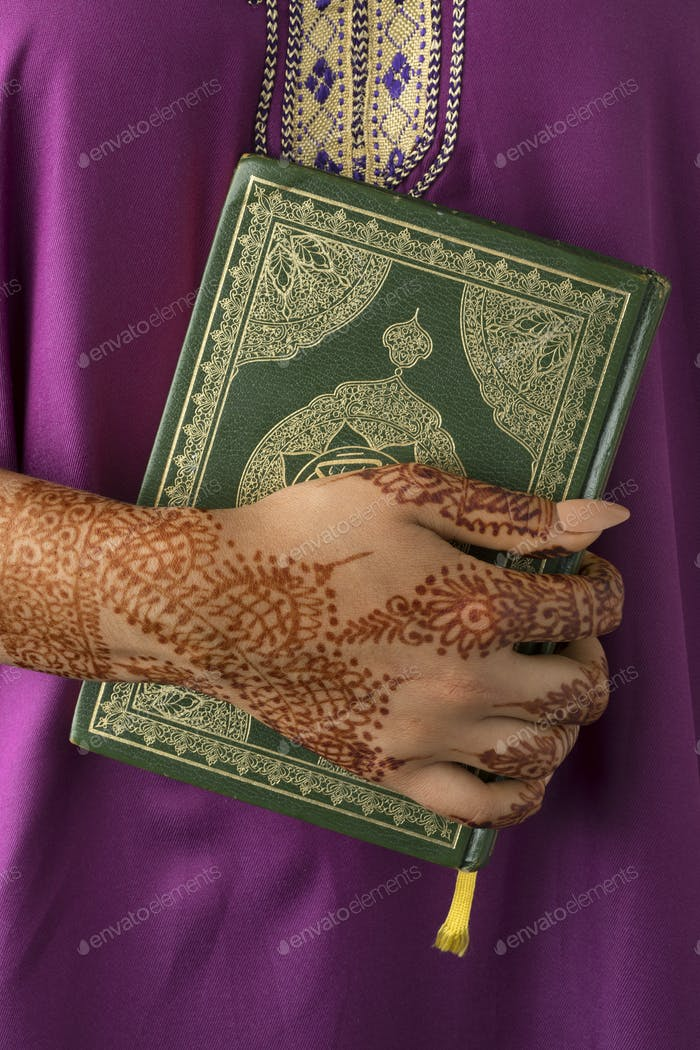 Moroccan woman with henna painted hands holding a koran