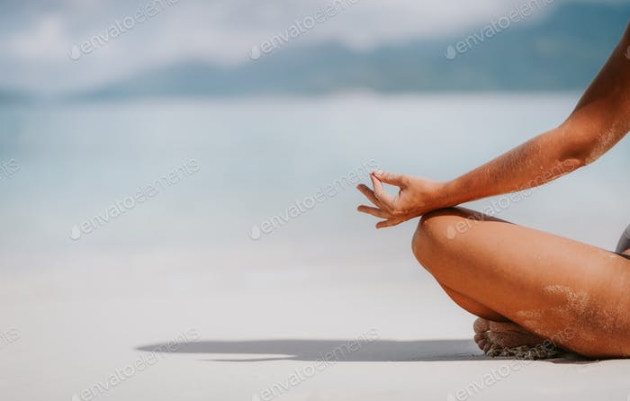 Rear view of a woman hands and legs in meditating pose on sandy beach. Tropical recreation vacation
