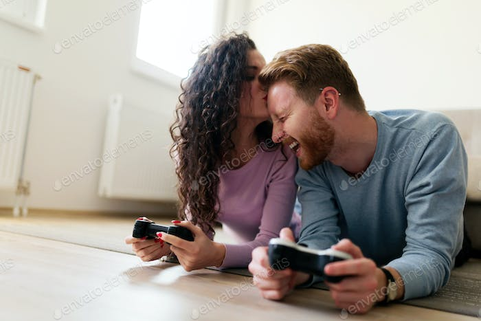 Happy couple playing video games at home