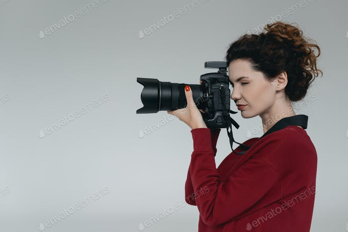 professional female photographer with digital photo camera in photo studio, isolated on grey
