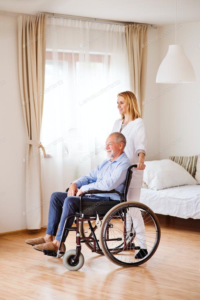Krankenschwester und Senior Mann im Rollstuhl während des Heimbesuchs.