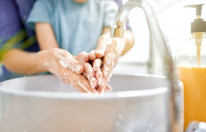 Kind und Erwachsene waschen ihre Hände