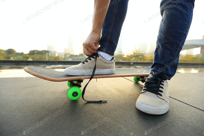 skateboarder tying shoelace on city