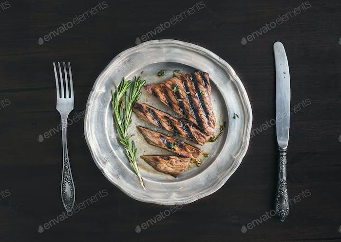 Rindersteak in Stücke geschnitten mit Rosmarin, Messer und Gabel auf einem vi