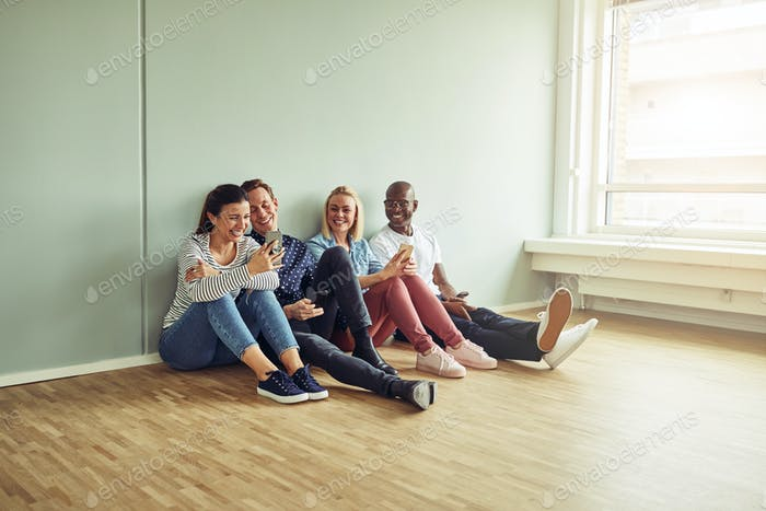 Young businesspeople sitting on an office floor taking a break
