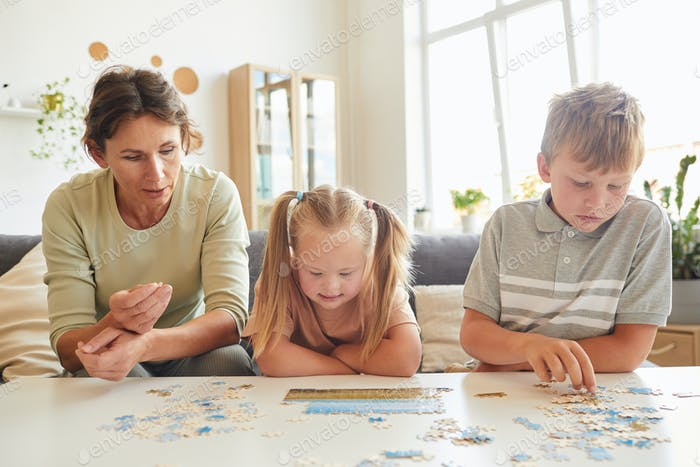 Girl with Down Syndrome Playing Puzzle Game with Family