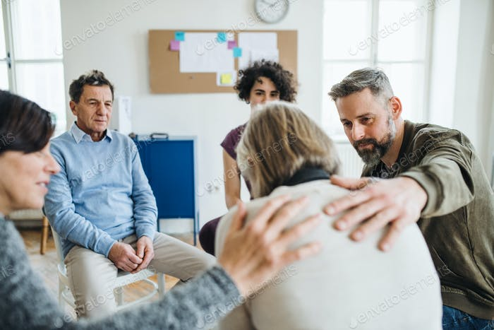 Men and women sitting in a circle during group therapy, supporting each other.