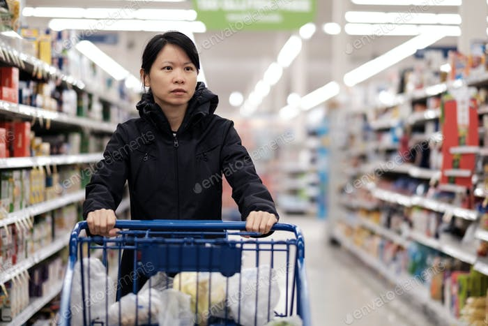 Asian woman doing groceries shopping in supermarket