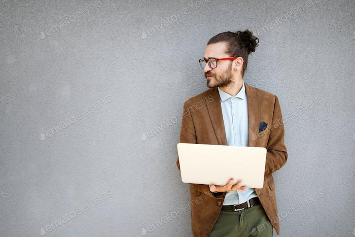 Glückliche junge Unternehmen männliche Führungskraft mit digitalem Tablet vor grauen Hintergrund