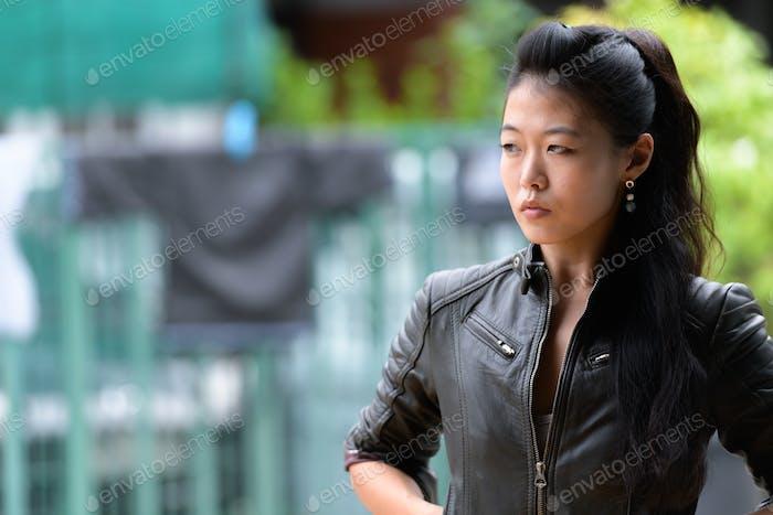 Porträt von schönen asiatischen rebellischen Frau denken im freien