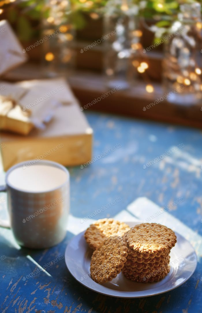 Teacup and Christmas gluten free cookies on a table near the decorated window with gift boxes