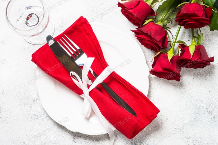 Romantic holiday table setting with plate, roses and present.