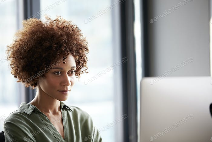 Young black female creative sitting at a desk looking at computer monitor, close up