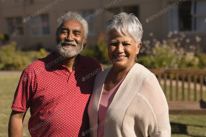 Front view of active senior couple smilling and standing in the park at nursing home