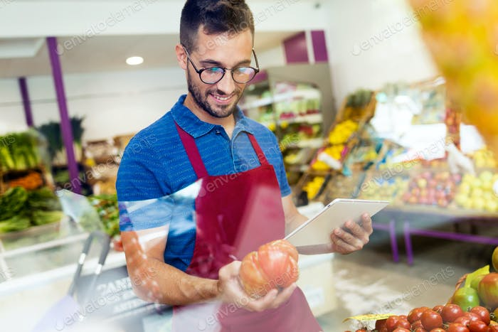 Salesman selecting fresh tomatoes and preparing for working day