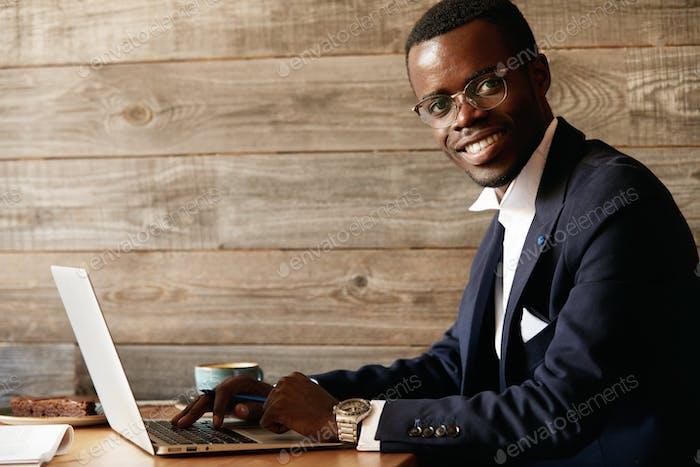Junge attraktive lächelnde afrikanische Männer, die eine Nachricht über soziale Netzwerke auf dem Laptop eingeben und an einem