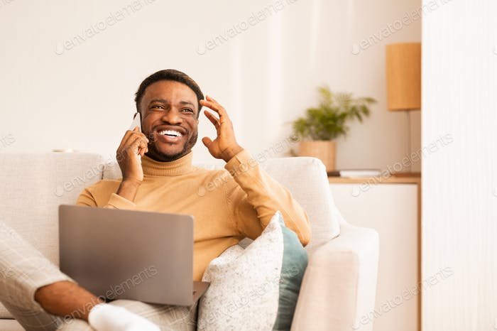 Man Using Laptop Talking On Phone Sitting On Sofa Indoor