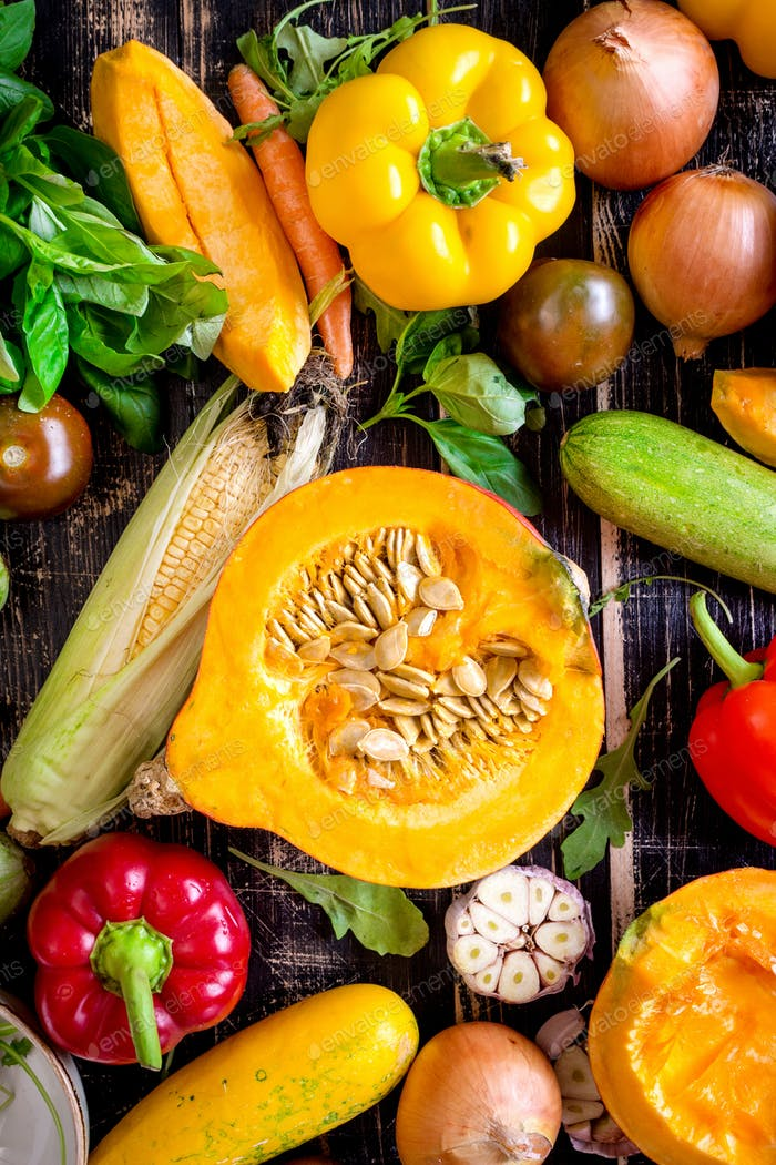 Fresh vegetables scaterred on a rustic dark textured table. Autumn background