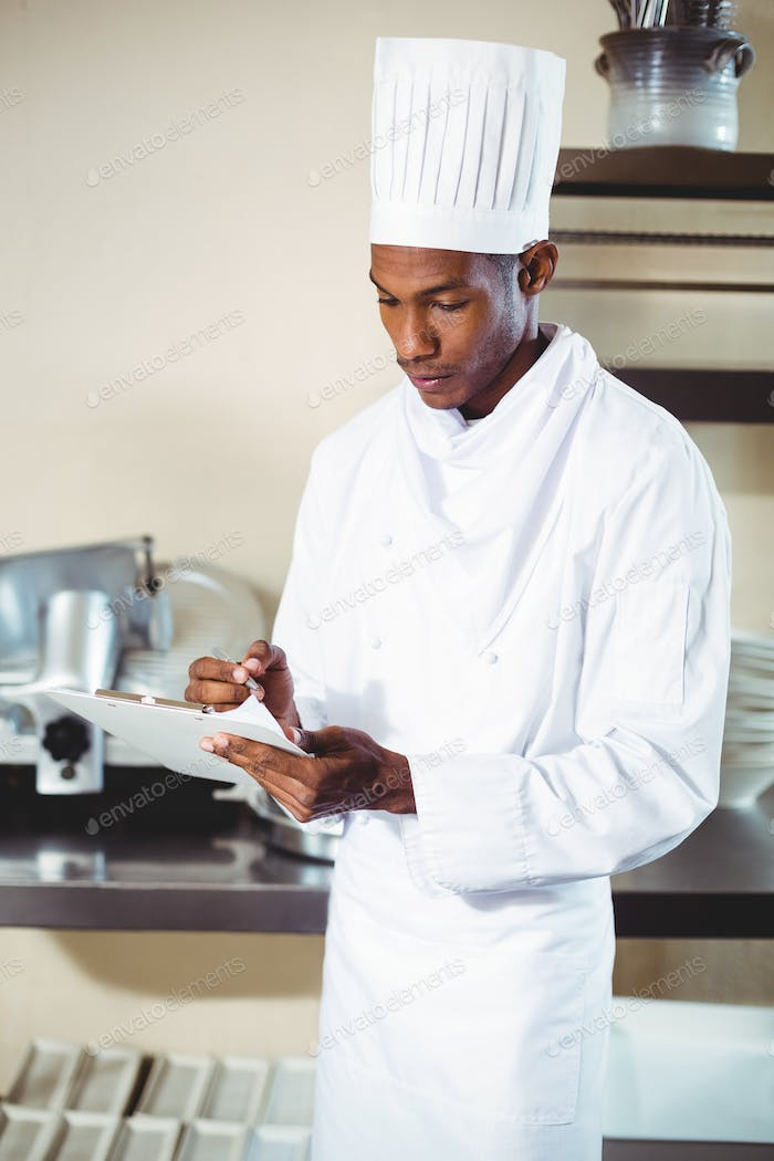 Chef writing notes on a clipboard