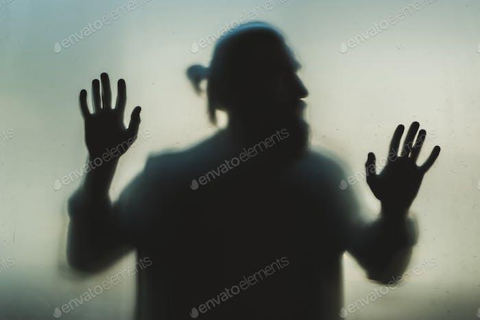 Silhouette des Menschen hinter Milchglas