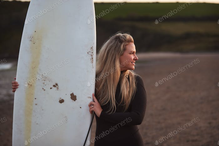 Woman Wearing Wetsuit Holding Surfboard Enjoying Surfing Staycation On Beach As Sun Sets