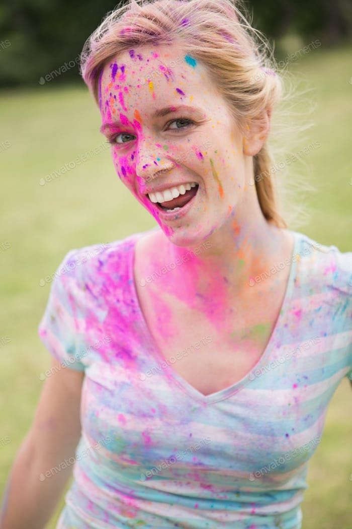 Young woman having fun with powder paint on a sunny day