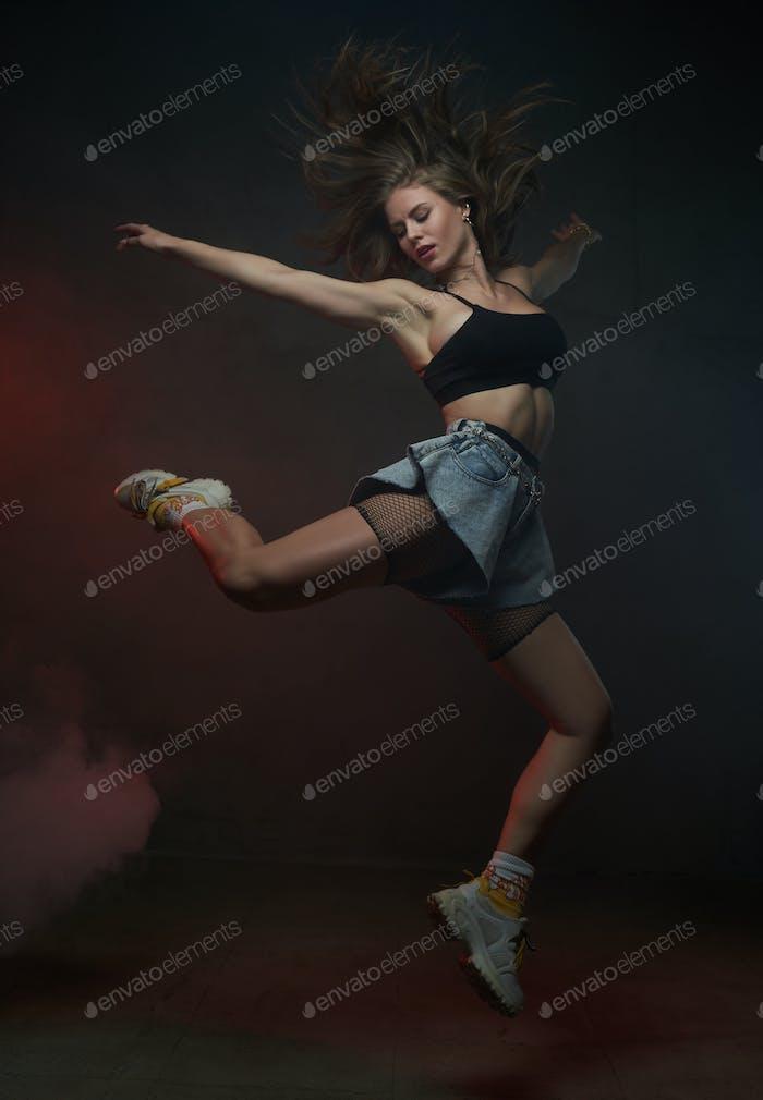 Jumping female dancer in short clothing in dark background