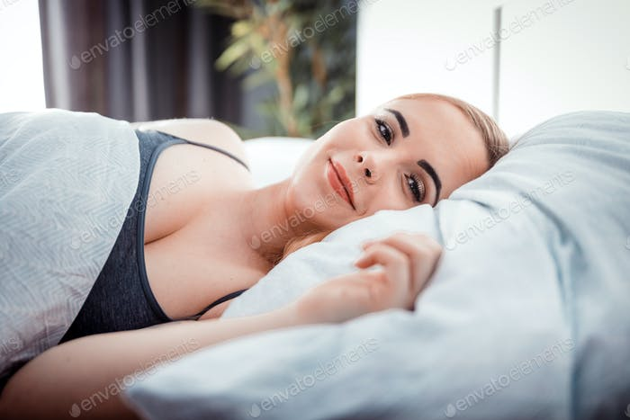 Natural woman peacefully lying in bed on soft pillow, looking at camera