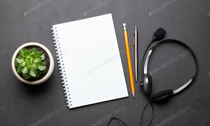 Office desk with headset and notepad