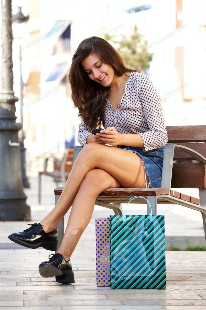 Glückliche Frau sitzt draußen mit Handy und Einkaufstaschen