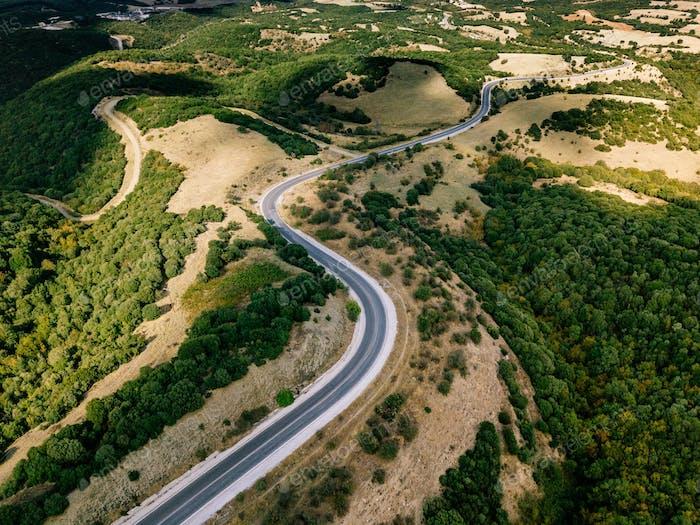 Aéreo por encima de un Horizontal rural con una Carretera curvilínea que pasa a través de ella en Grecia.