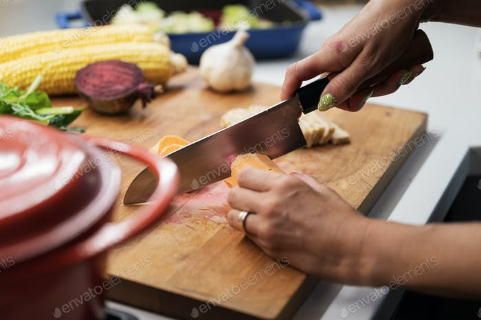 Cutting sweet potato on a wooden kitchen board full of various autumn vegetables