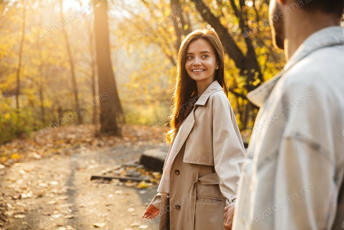 Beautiful smiling young couple walking in the autumn park