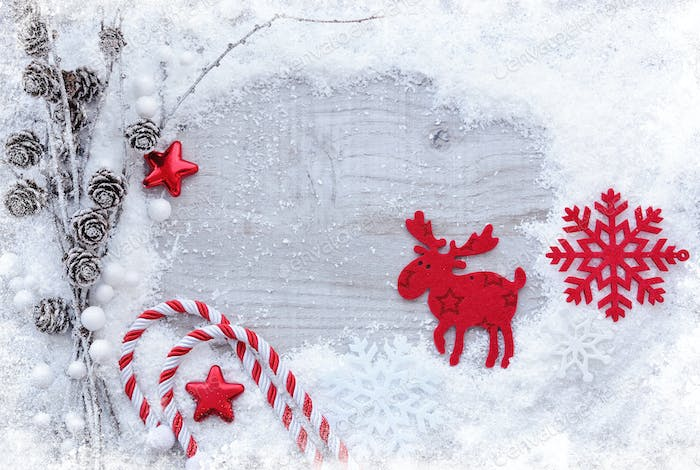 Greeting card with snow and christmas decorations on wooden back