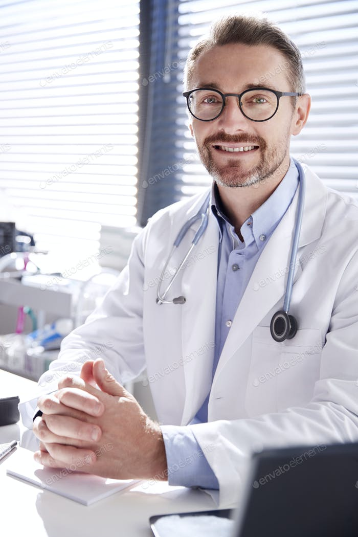 Portrait Of Smiling Male Doctor Wearing White Coat With Stethoscope Sitting Behind Desk In Office