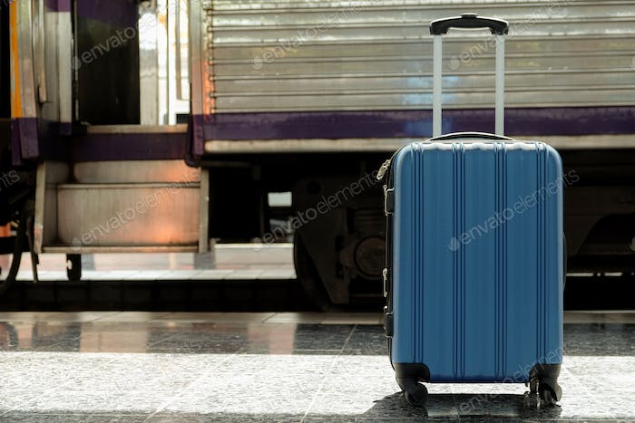 The blue suitcase is placed on the train platform.