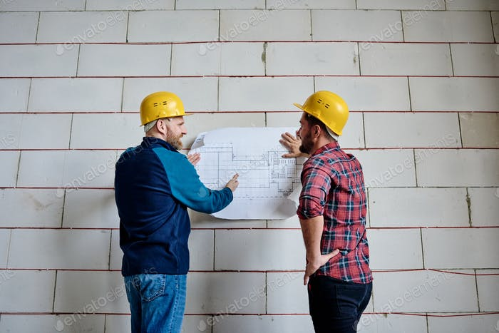 Two successful builders in protective helmets discussing blueprint by wall