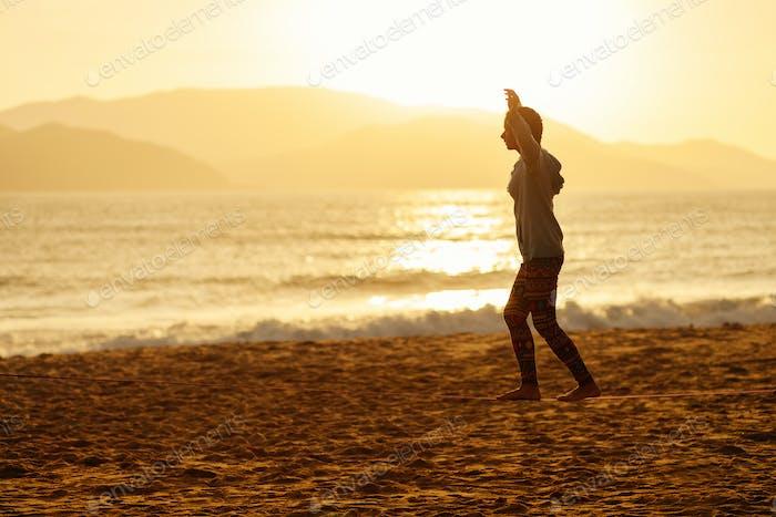 Teenager-Mädchen Balance Slackline Silhouette am Strand