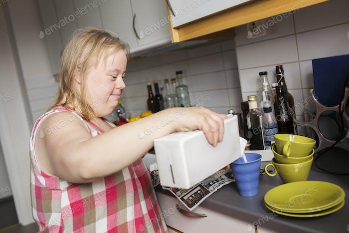 Frau mit Down-Syndrom Gießen Milch auf Becher in der Küche