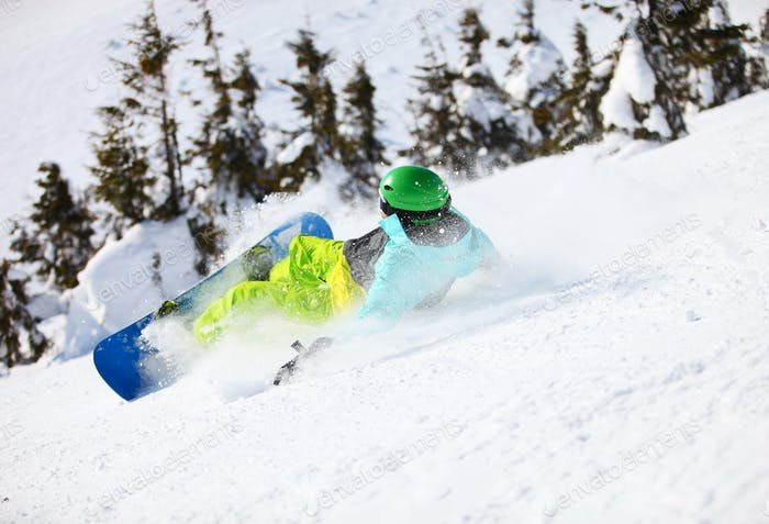 Young male snowboarder after falling on a mountain slope